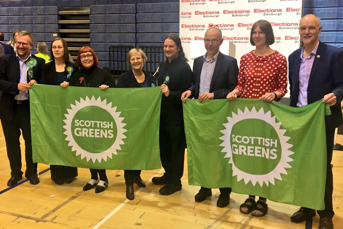 8 Green winning councillors at the Edinburgh count, holding Scottish Green flags