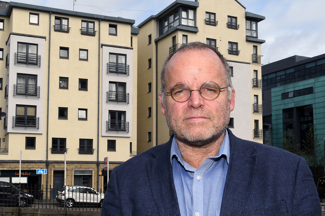 Andy Wightman in front of a modern block of flats
