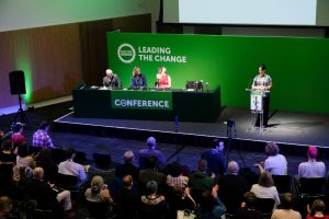 Scottish Green Party conference speakers with banner 'Leading the change'