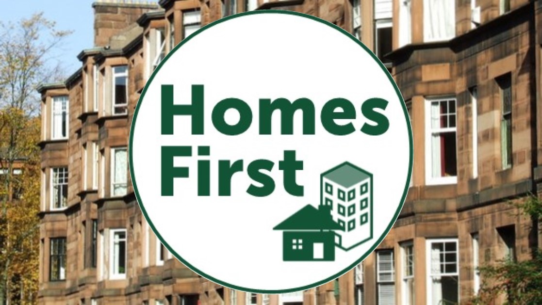 Homes First logo over photo of tenements