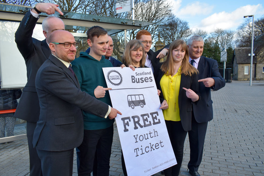 Green MSPs (Patrick Harvey, Mark Ruskell, Andy Wightman, Alison Johnstone, Ross Greer and John Finnie) and two young greens (Cameron Glasgow and Gillian Mackay) holding a giant free youth bus ticket.